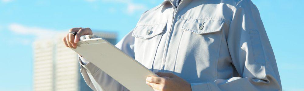青空の下で働く作業服の男性